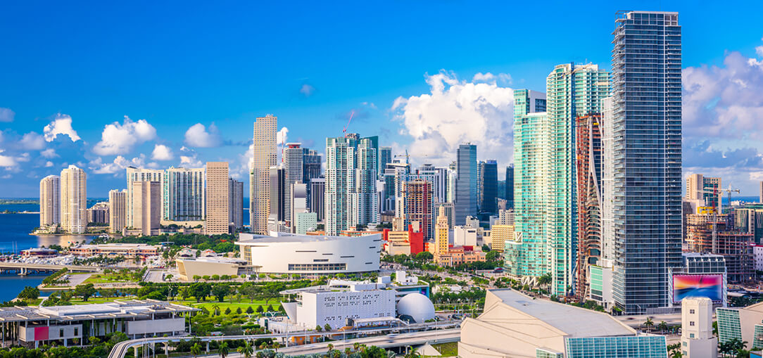 View of downtown Miami, Florida with tall buildings and the ocean in the distance on sunny day.