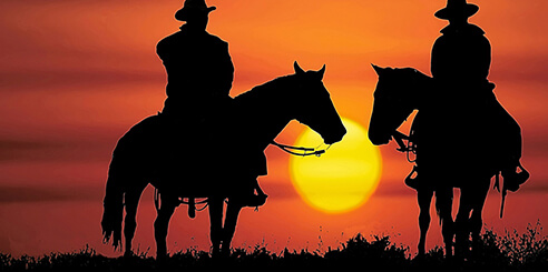The silhouettes of two cowboys on horses in the desert at sunset near Las Vegas.