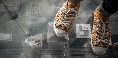 A pair of cheetah print sneakers on Skydeck in Chicago with the city street visible below.