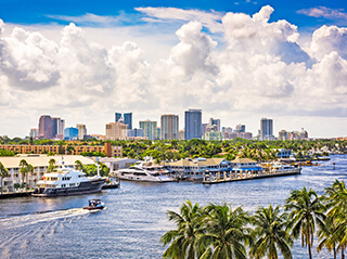 View of the Fort Lauderdale city skyline against a sunny midday sky with white clouds.