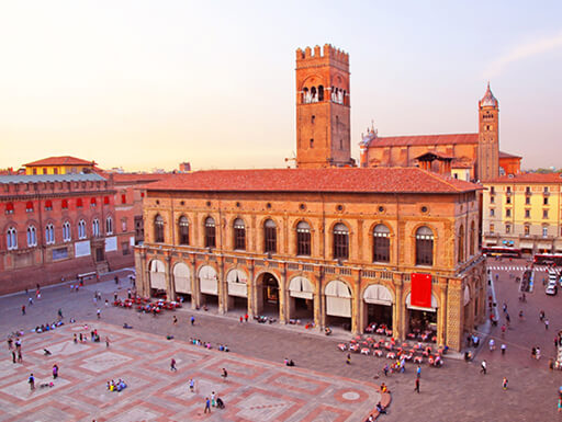 Bologna's main square dotted with pedestrians and King Enzo palace in the early evening sunset in Italy.