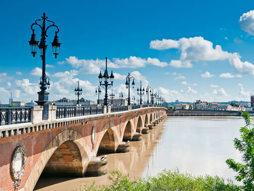View of Pont de Pierre, an old stone bridge with rod-iron railings and lamp posts on a sunny afternoon in Bordeaux, France.