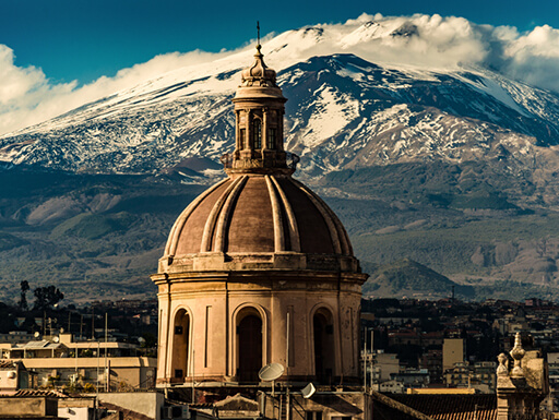 The cathedral dome of Catania with Mount Etna in the background on a bright afternoon in Catania, Italy.