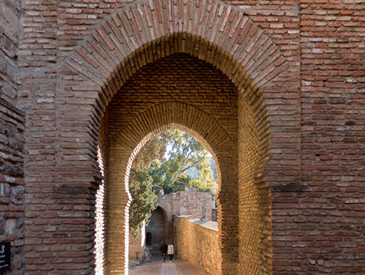 An arched, red brick doorway in the Alcazaba in Malaga, Spain during a sunny day.