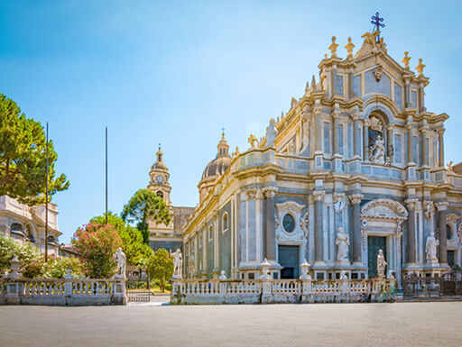 Piazza del Duomo with a focus on the beautifully gold and blue Cattedrale di Sant'Agata on a sunny afternoon in Catania, Sicily.
