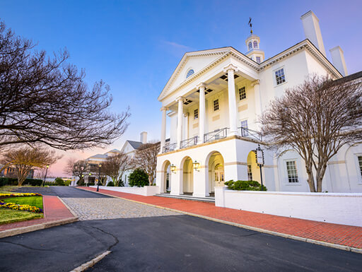 An historic white building with arched entryways and large columns on the front in Richmond, Virginia