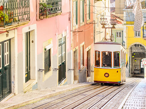 Sleepy Bairro Alto during the day, flanked by pastel houses and the city's iconic yellow vintage tram