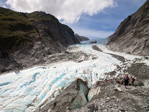 The icy, river-like glacier of the Franz Josef Glacier cuts through the mountains in New Zealand, with a cloudy blue sky in the background