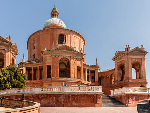 The Sanctuary of the Madonna di San Luca is a beautiful stone building sitting under the bright sun in Bologna, Italy.