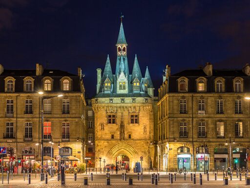 Porte Cailhau is a beautiful stone building illuminated at night in Bordeaux, France.
