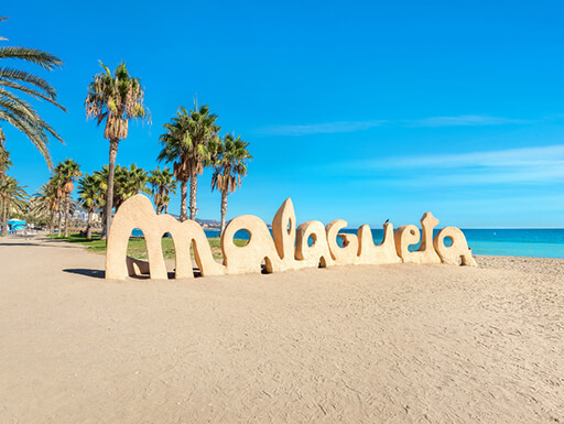 Malagueta beach with a sand sculpture spelling the beach name and palm trees lining the shore on a sunny afternoon in Malaga, Spain.