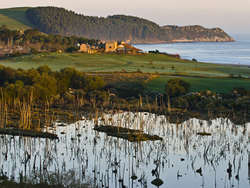 Water and fields of Oyambre Natural Park in San Vicente de la Barquera, Spain at dusk