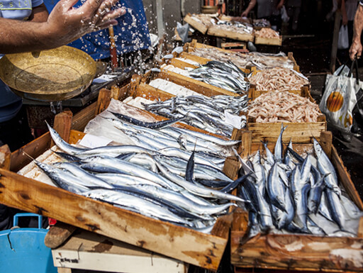 A stall with wooden crates of silverfish for sale is surrounded by sellers and shoppers at the fish market – La Pescheria – in Catania.
