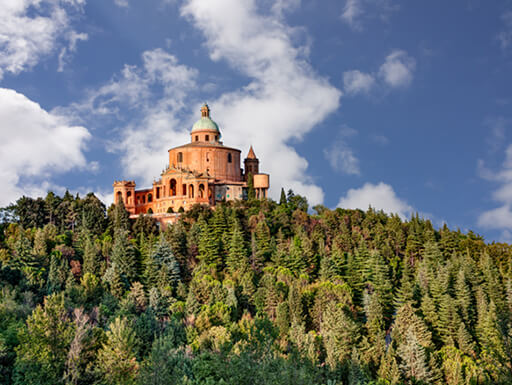 Sanctuary of the Madonna di San Luca on the top of a hill, surrounded by trees on a sunny day in Bologna, Italy.