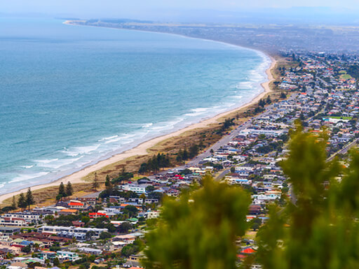 The city of Mount Maunganui runs along the curved, sandy beach alongside the light blue ocean with waves rolling in, in New Zealand