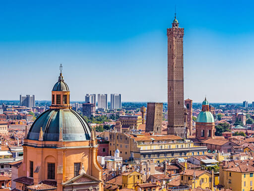 Panoramic view of the downtown buildings and rooftops of Bologna, Italy on a clear, sunny afternoon.