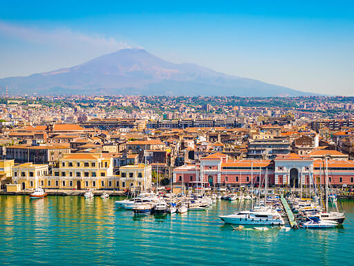 A view of Catania, Sicily, with boats in the harbor and Mount Etna in the background on a beautifully sunny day.
