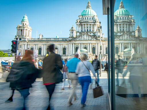 Blurred view of people walking through the center of Belfast in front of the city hall in Northern Ireland on a clear day.