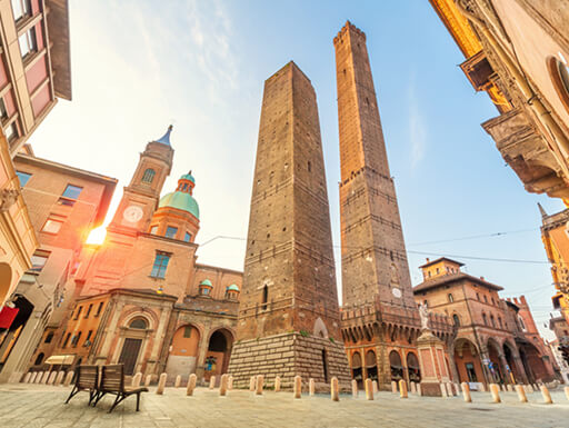 Bologna's famous leaning towers – Torre degli Asinelli and Torre Garisenda – stand tall on a sunny day in Bologna, Italy.