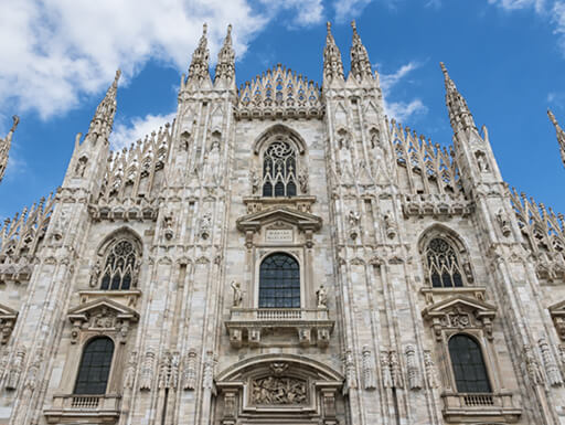 Gothic church Duomo di Milano with blue sky and white clouds in the background