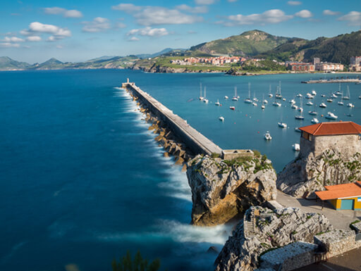 Long exposure of Breakwater and harbor in Castro Urdiales, Spain shows mountains and blue sky with white fluffy clouds in the background