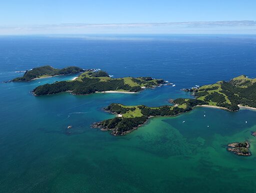 An aerial view of three small islands covered in plant life, surrounded by aqua blue and green waters in the Bay of Islands in New Zealand
