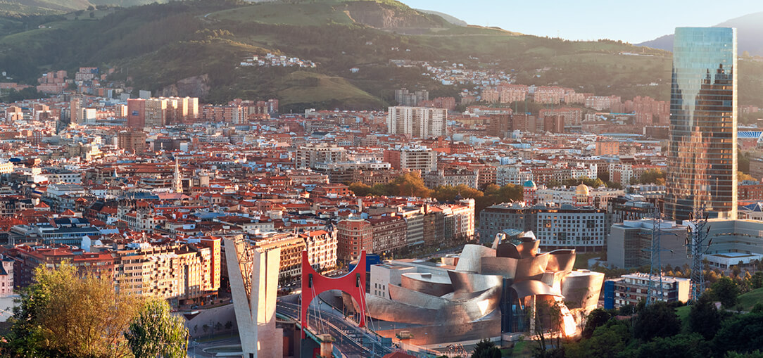 An aerial view from the mountains of the city of Bilbao, Spain on a sunny day with mountains in the background.