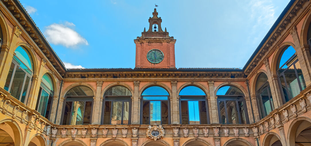 The exterior of the Archiginnasio of Bologna with intricate columns and windows reflecting the bright blue sky in Italy.