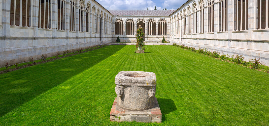 A sunny daytime view of Camposanto Monumentale cemetery in Pisa with lush, green grass.