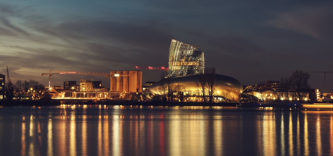 Nighttime view from across the Garrone River of the Bordeaux wine museum, illuminated and reflecting off of the water.