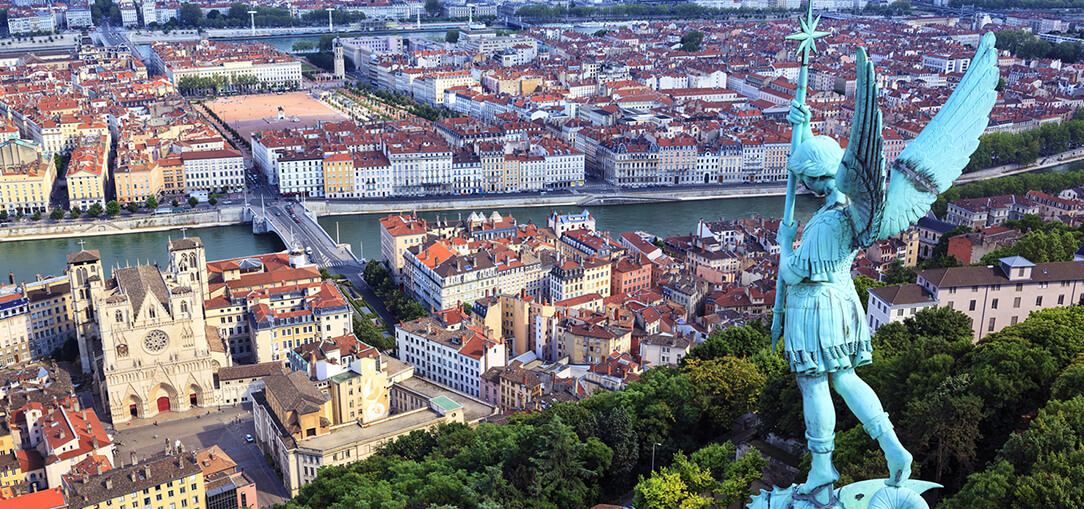 An aerial view of Lyon, France from Notre Dame de Fourvière with a bronze statue in the foreground.