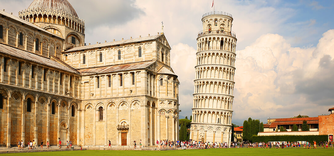 The famous Leaning Tower of Pisa is surrounded by visitors next to the Pisa Cathedral in the Square of Miracles on a sunny day in Pisa, Italy.