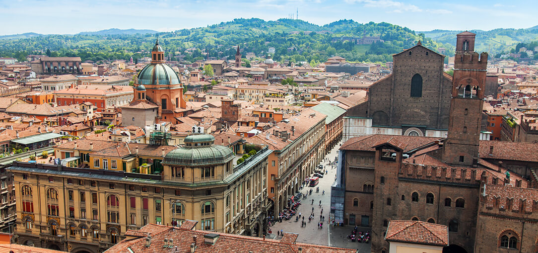 An aerial view of Bologna's old city shows the red roofs and impressive architecture with mountains in the distance on a sunny afternoon in Italy.