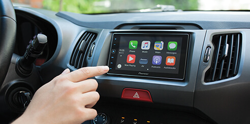 Man in car reaching for touchscreen multimedia infotainment system.