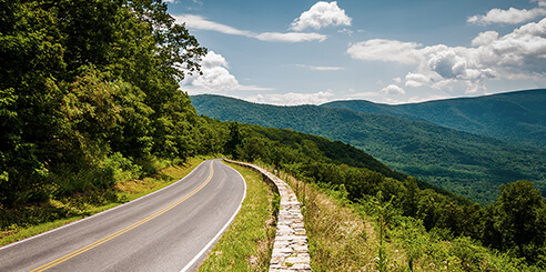 An empty road on side of mountain overlooking the Blue Ridge Mountains on a sunny day in Virginia