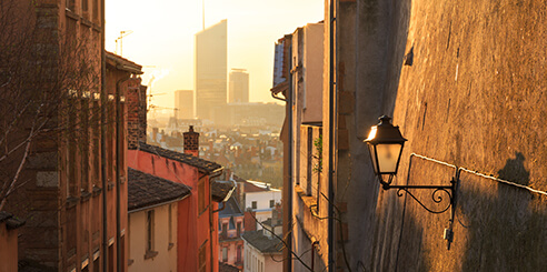 Aerial view at sunrise of a narrow alley in Vieux Lyon, looking onto Part Dieu's architecture.