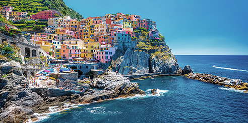 Vibrantly colorful buildings sit on a cliff overlooking the sea in Cinque Terre, Italy