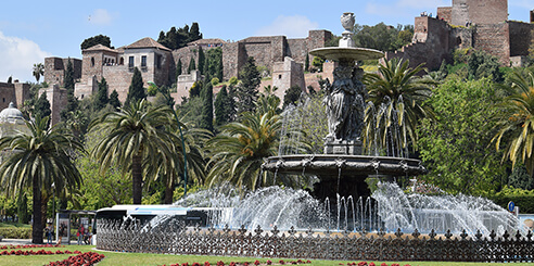 View of the Alcazaba fortress in Malaga, Spain on a clear day with a large fountain and green palm trees in the foreground.
