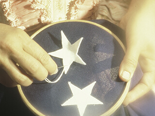 A woman's hands are pictured in an aged photo sewing stars on to fabric depicting the creation of the first American flag by seamstress Betsy Ross, who has a home visitors can tour in Philadelphia