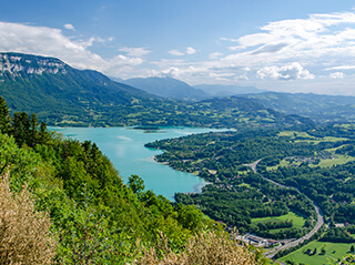 An aerial view of Lac D'aiguebelette's emerald water surrounded by lush green forests and mountains near Lyon, France.