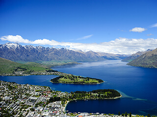 The buildings from the city of Queensland are seen on the edge of the bright blue waters of Lake Wakatipu in New Zealand, with snow-capped mountains and a bright blue sky in the background