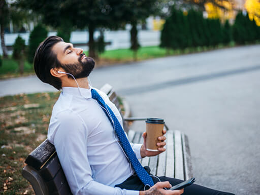 A businessman on a break from work takes a moment to close his eyes and practice mindfulness while sitting on a park bench on a fall afternoon.