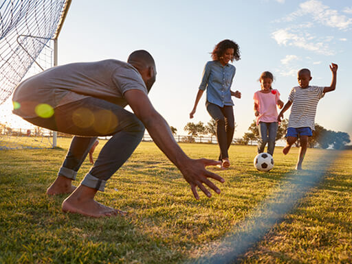 "Alt = ""A mom and dad play a barefoot game of soccer with their son and daughter on a warm afternoon"