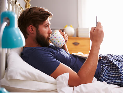 A man scrolls aimlessly on his phone first thing in the morning while drinking coffee in bed.