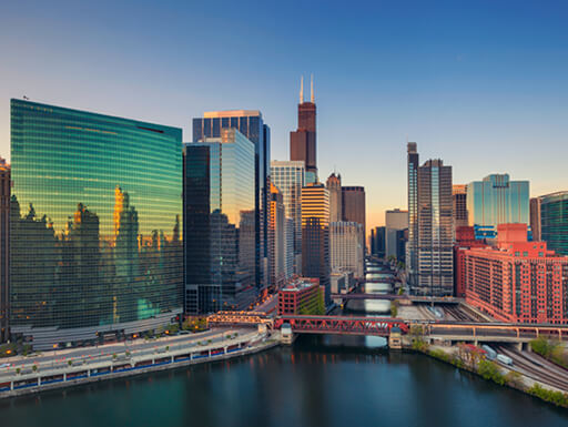 Panoramic view of the Chicago cityscape over the water at dawn.