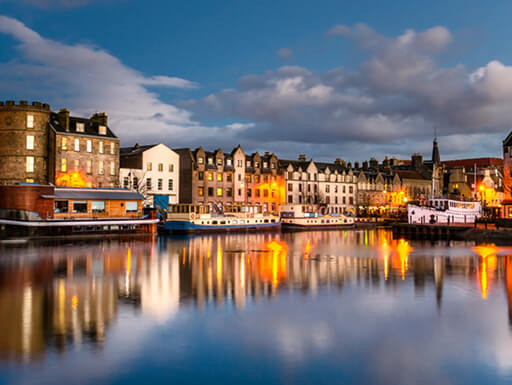 Buildings reflect in the water at the Old Leith Docks