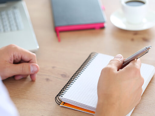 A hand holds a silver pen above a blank page of a notebook, about to start making a to-do list.