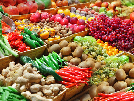 "Alt = ""Rows of colorful, vibrant fruits and vegetables shine at Eastern Market on a bright day."