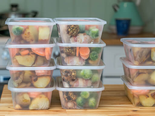Stacks of Tupperware containers with a week's work of pre-prepped lunches sits on a counter.