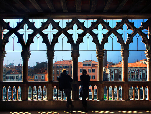 A couple enjoying the view of the Grand Canal from the balcony of Ca d'Oro